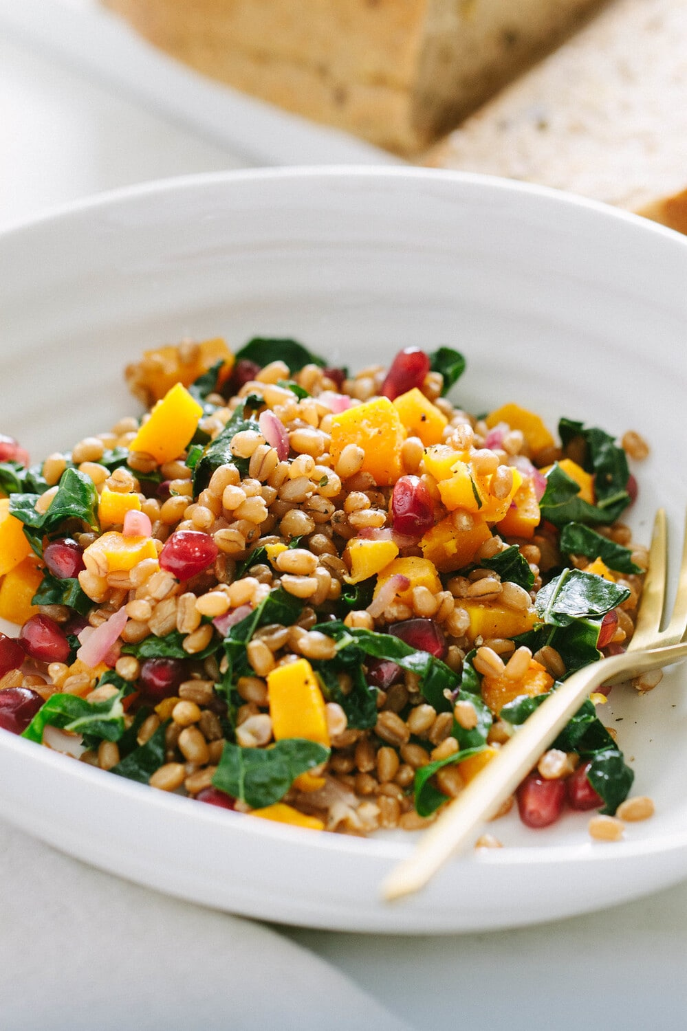side angle view of a serving of autumn wheat berry and butternut squash salad in a white bowl with gold fork.