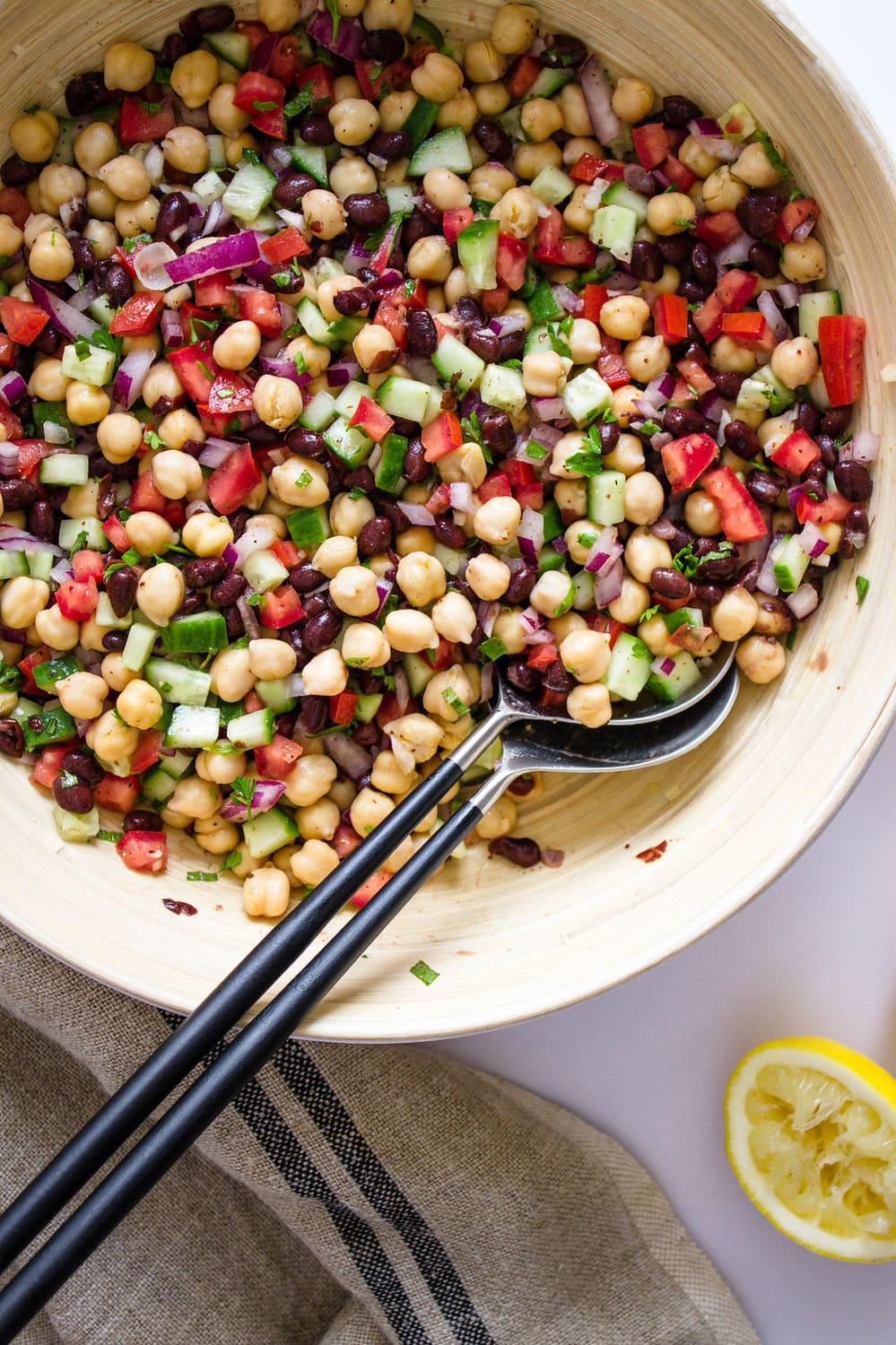 top down view of balela salad just mixed together in a large bamboo mixing bowl with silver utensils with black handles
