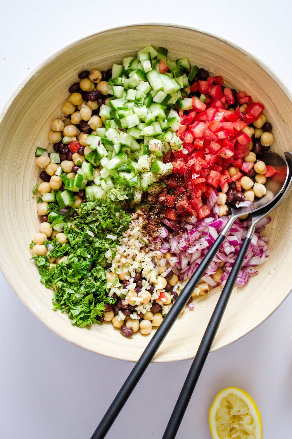 top down view of the ingredients for balela salad added to mixing bowl before mixing