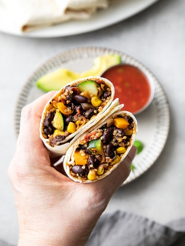 top down view of hand holding a black bean quinoa burrito sliced in half.