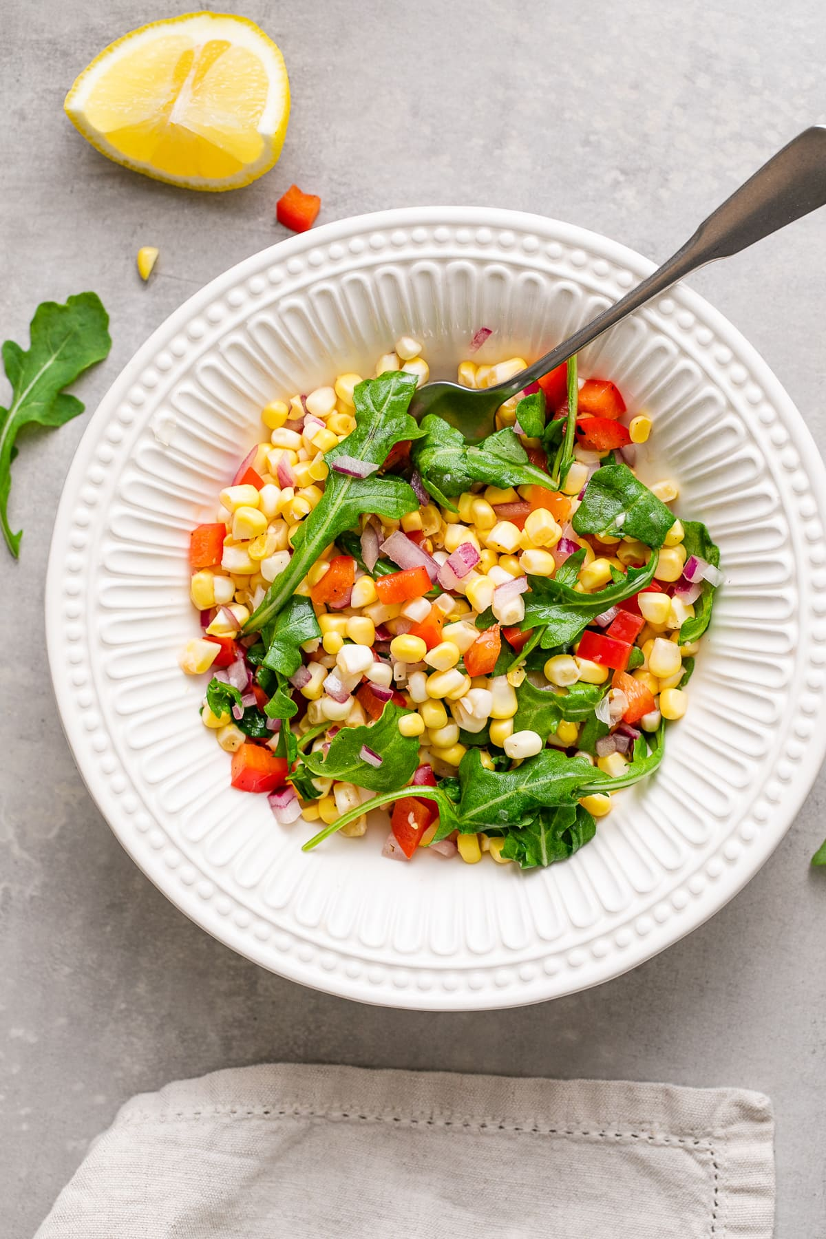 top down view of bowl with serving of corn arugula salad with items surrounding.