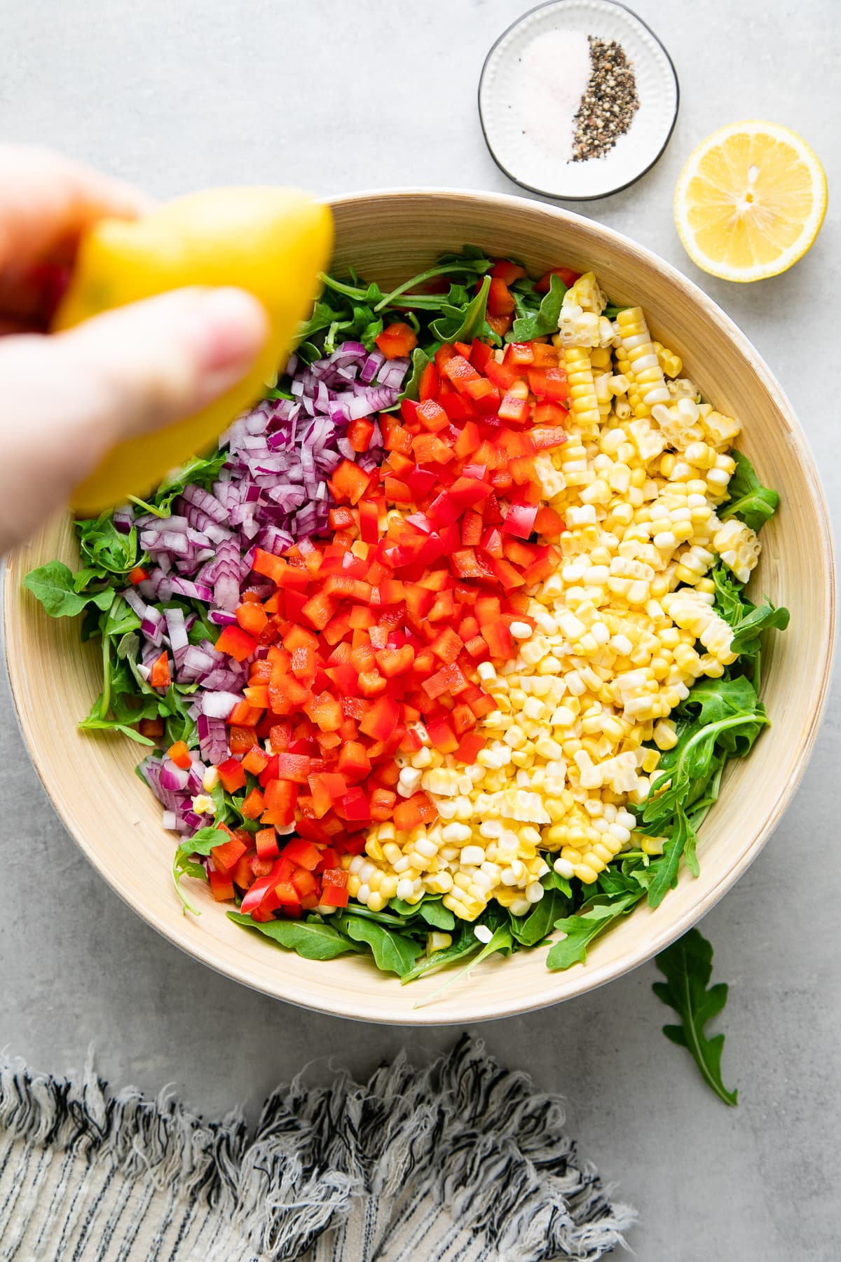 top down view of bowl with corn arugula salad ingredients added and lemon drizzled over top.