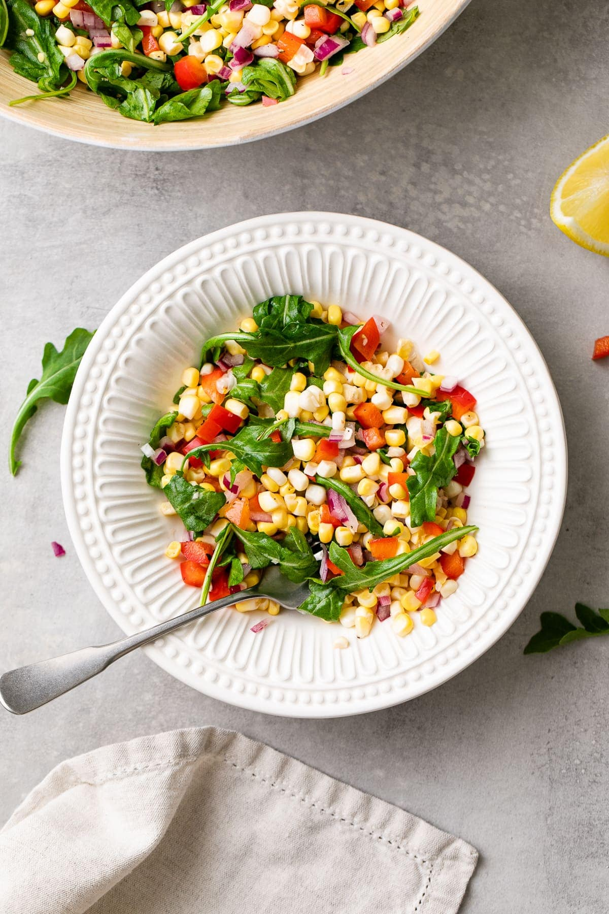 top down view of corn arugula salad in white bowl with fork and items surrounding.