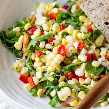 up close, top down view of a serving of corn and arugula salad in a white bowl with sliced bread.