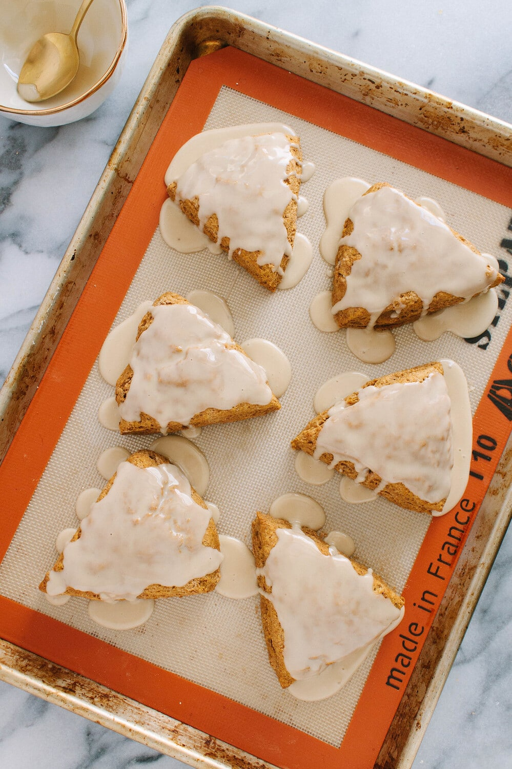top down view of vegan pumpkin scones on a baking sheet with vegan icing.