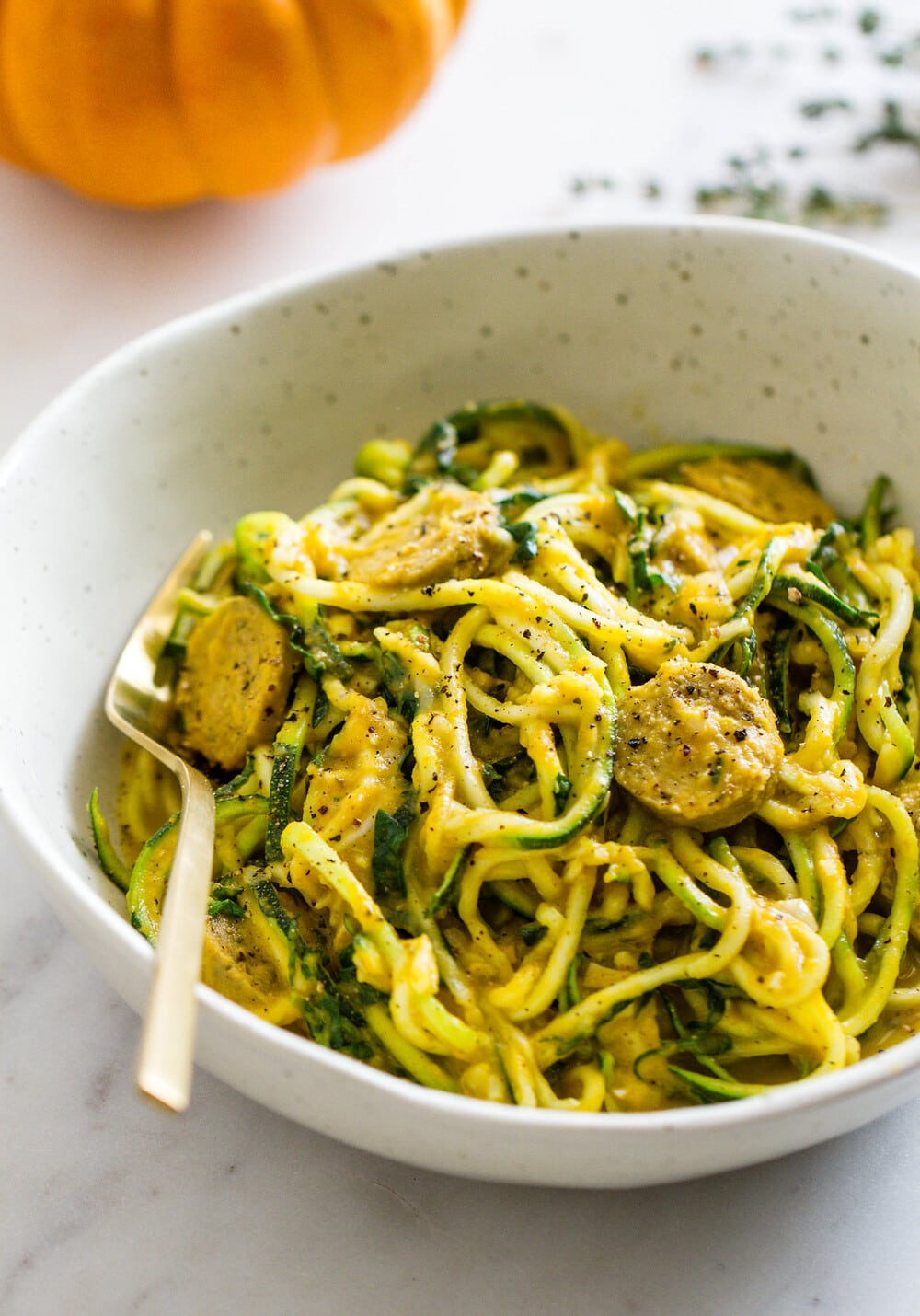 side angle view of creamy pumpkin sauce with kale and mushrooms, tossed with zucchini noodles.