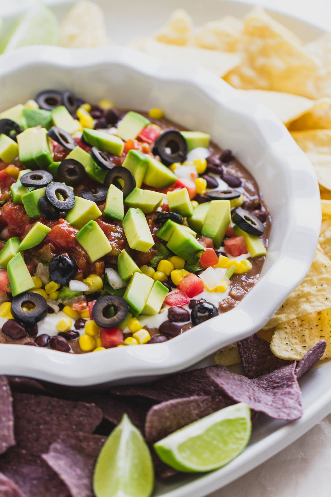 side angle view of vegan 7 layer mexican bean dip in a white dish surrounded by tortilla chips.