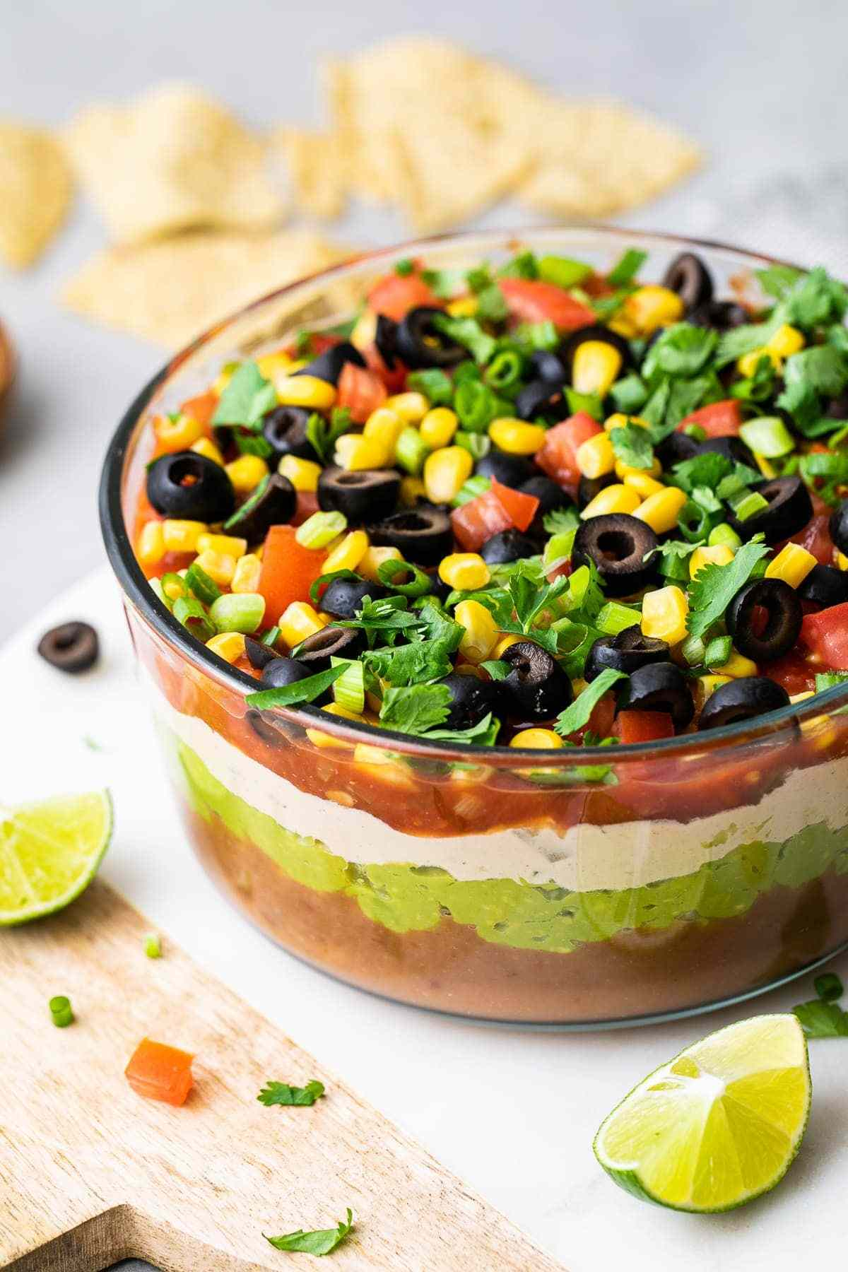 side angle view of vegan seven layer dip in glass bowl with items surrounding.