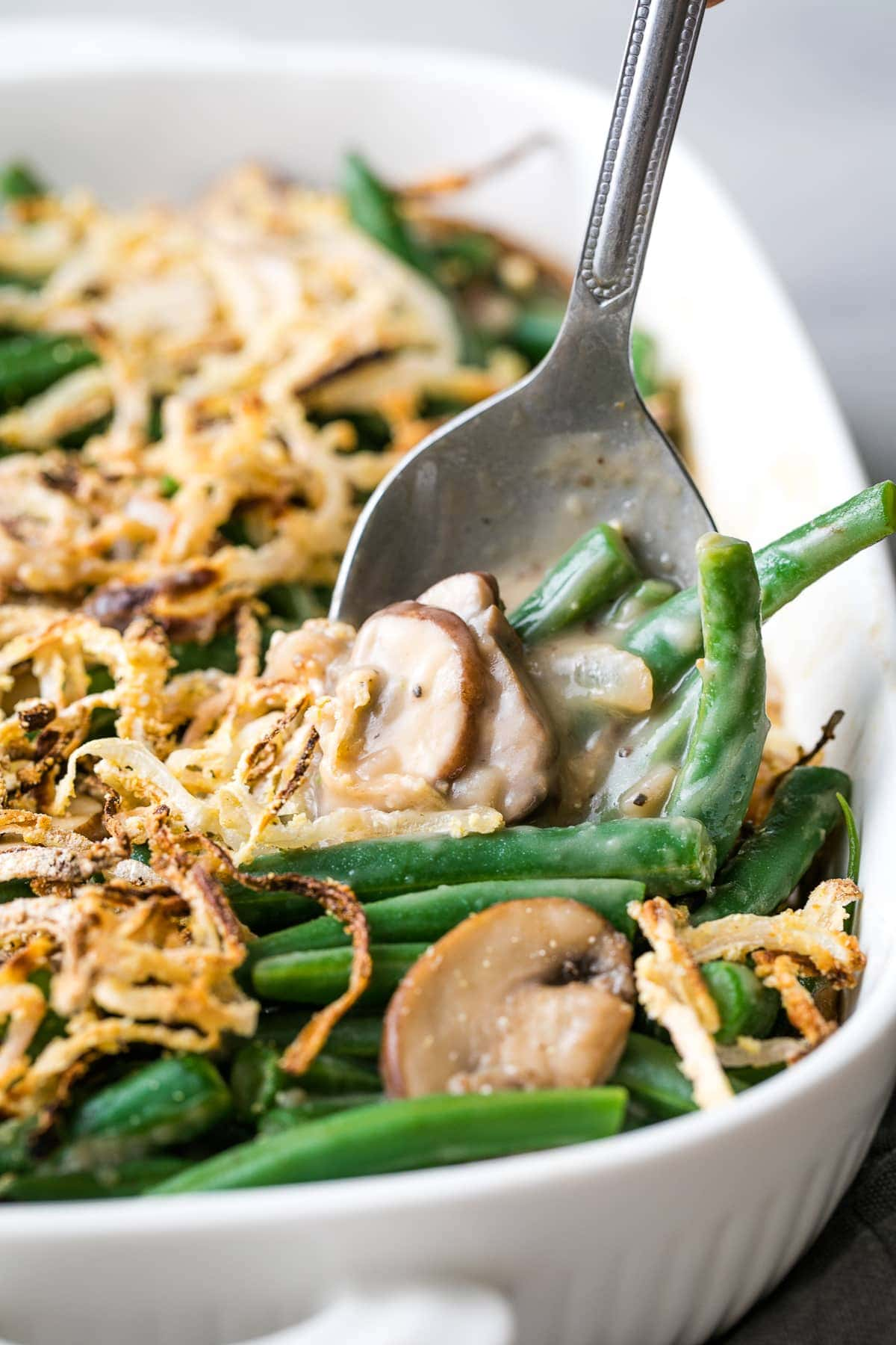 head on view of spoon scooping up vegan green bean casserole in a baking dish.
