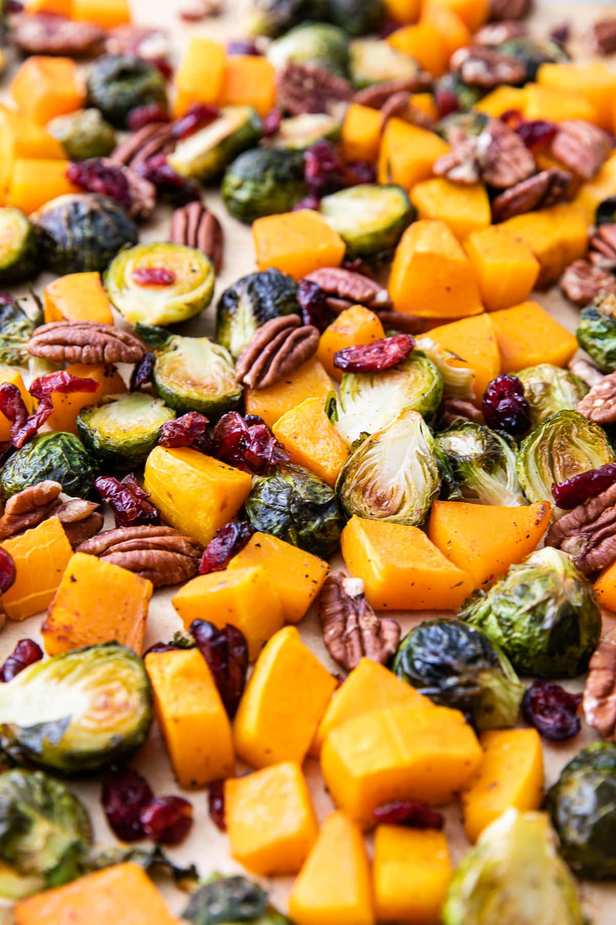 side angle view of freshly roasted brussels sprouts and butternut squash on a baking sheet.