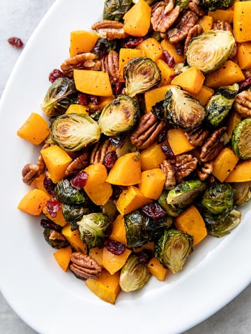 top down view of serving platter with roasted brussels sprouts and butternut squash with cranberries and pecans.