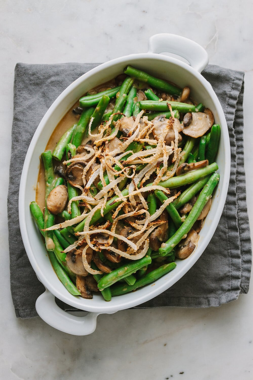 top down view of a white oval serving dish with healthy vegan green bean casserole.