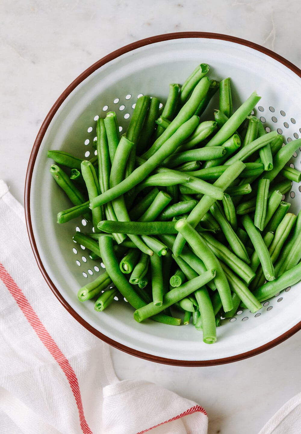 top down view of a white colander with fresh green beans.