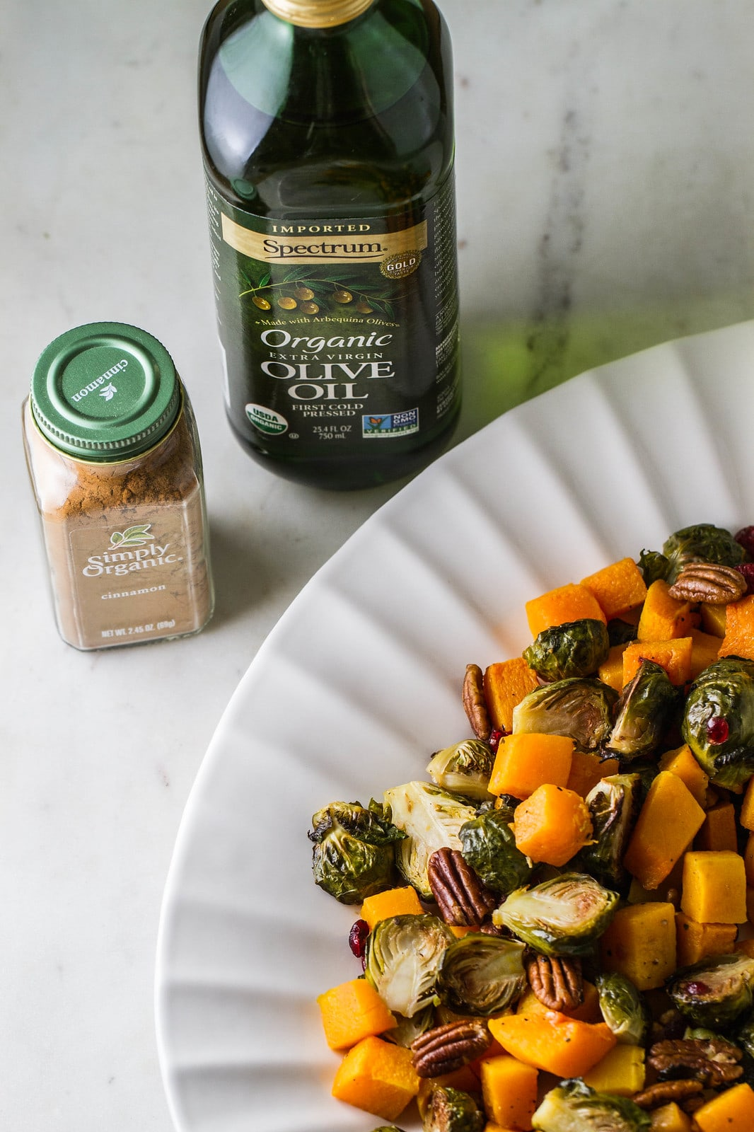 roasted butternut squash and brussels sprouts on a platter with items surrounding.