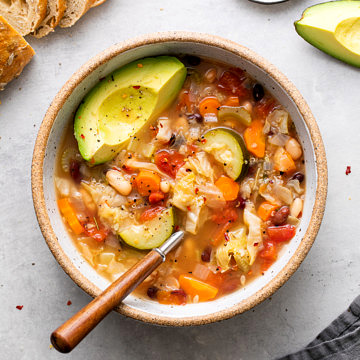 top down view of bowl of vegetable quinoa soup with spoon and items surrounding.