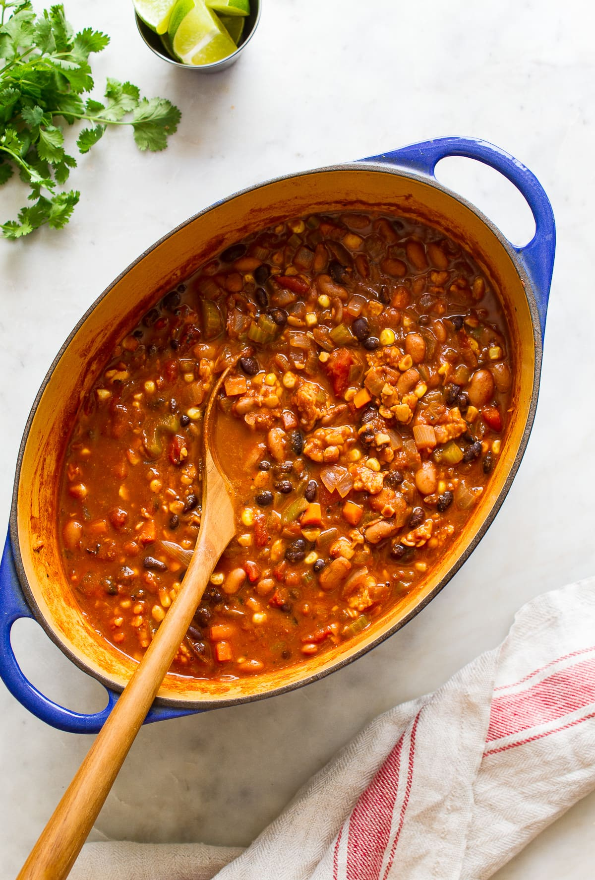 top down view of freshly made vegetable chili in a dutch oven with wooden spoon.