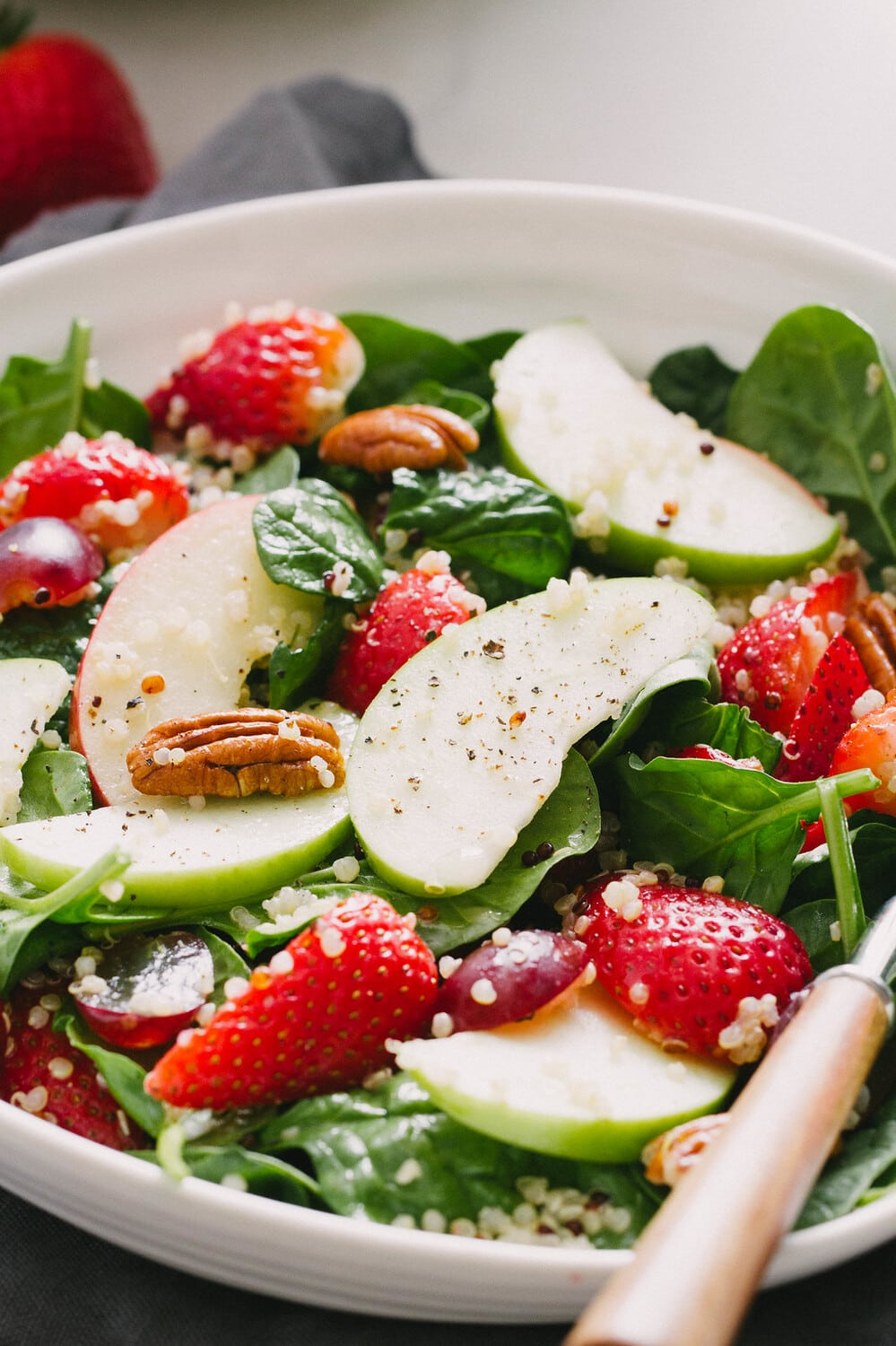 side angle view of spinach salad with strawberries, apples and quinoa.