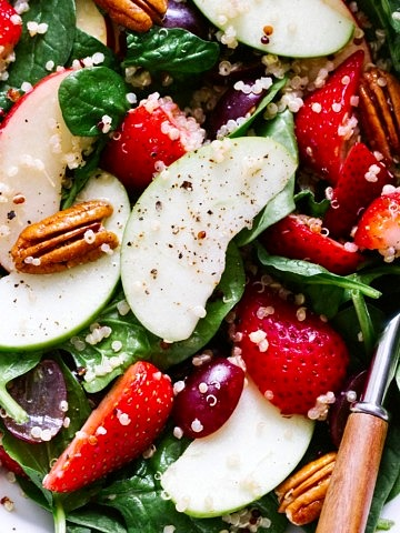 up close view of spinach salad with strawberries, apple and quinoa.