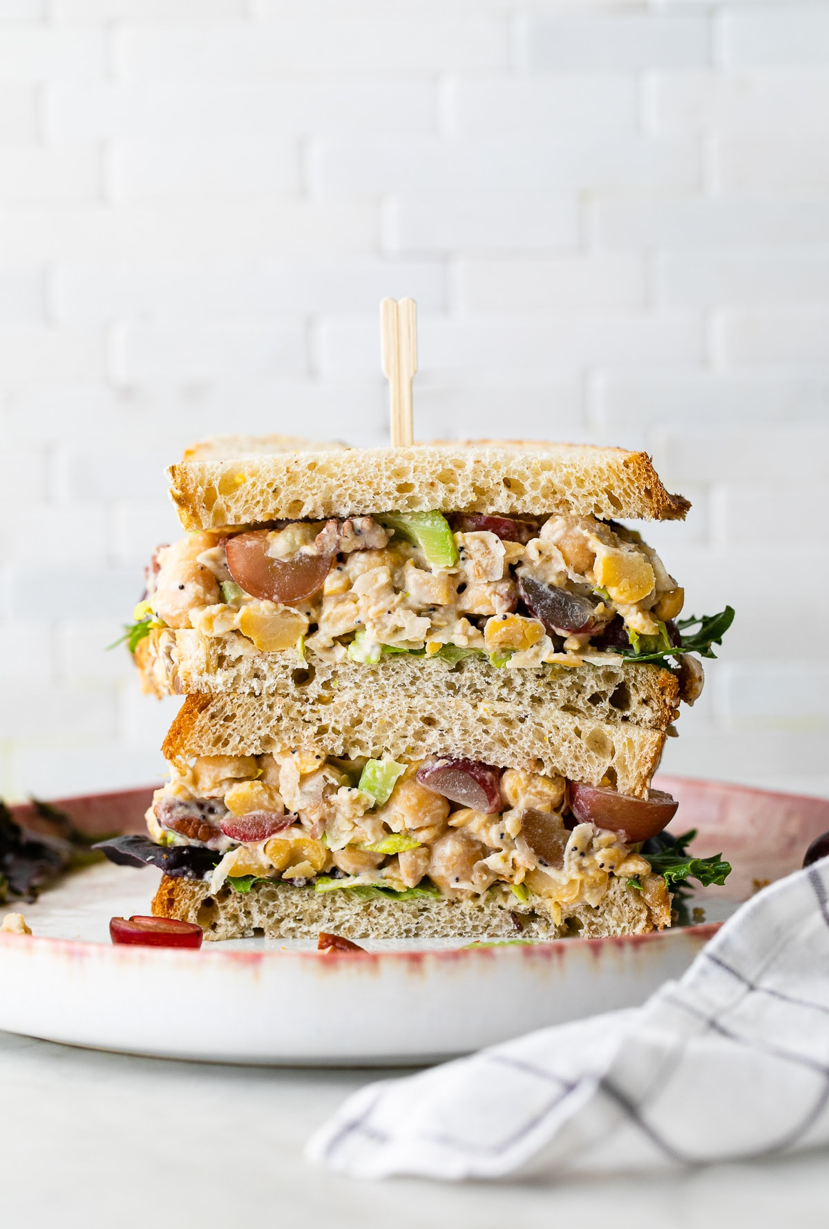 head on view of chickpea chicken salad sandwich sliced in half and stacked.