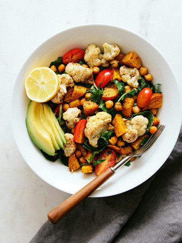 top down view of a bowl filled with a serving of roasted cauliflower, golden beet and chickpea salad.