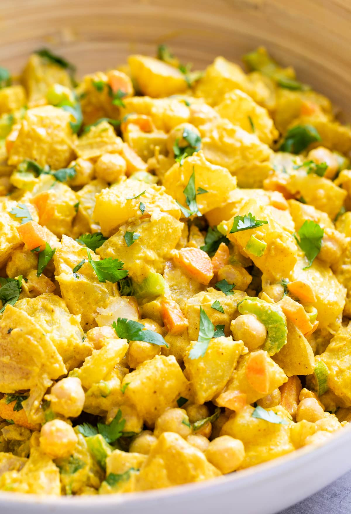 side angle view of vegan curried potato salad in a bowl.