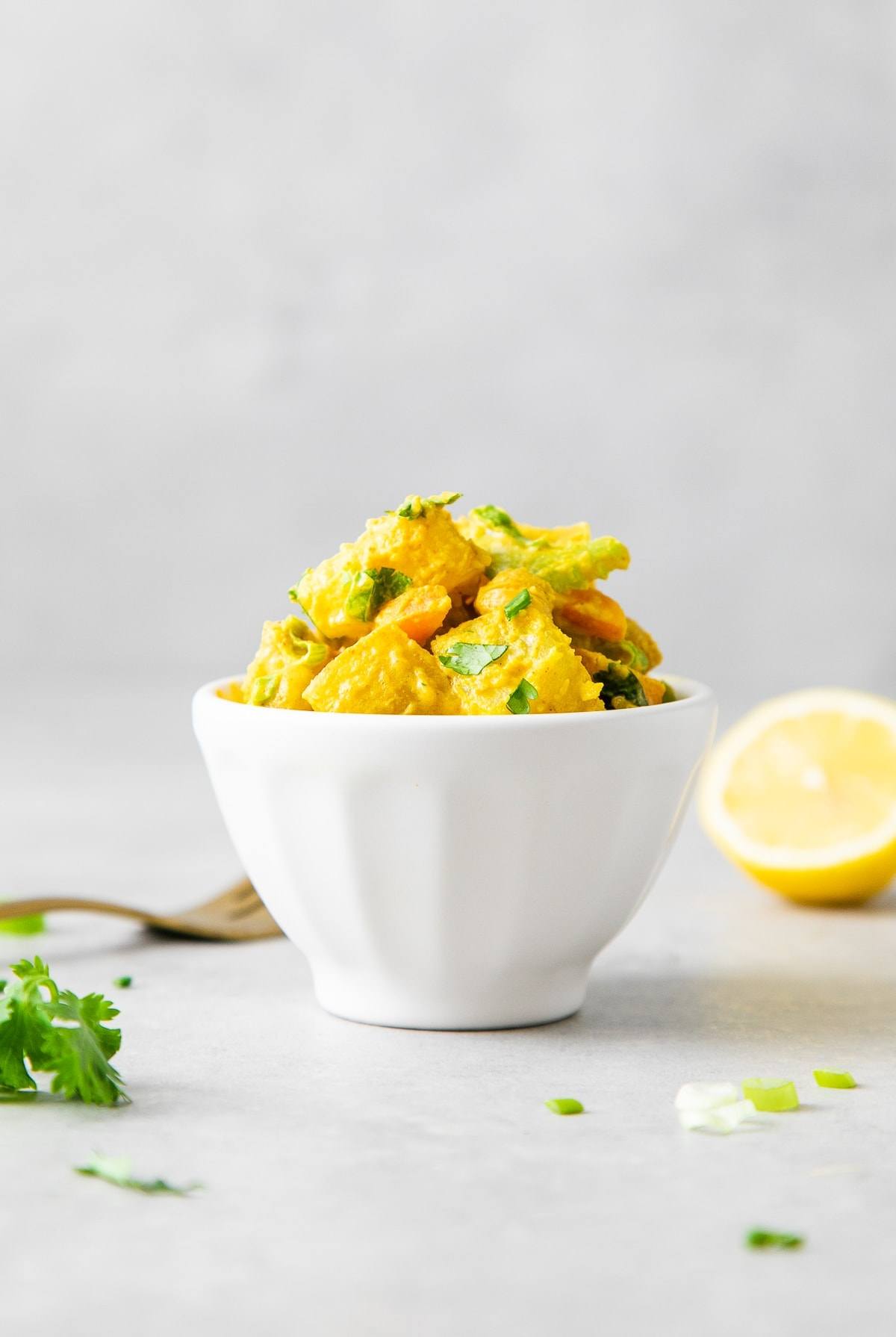head on view of healthy curried potato salad in a small white bowl with items surrounding.