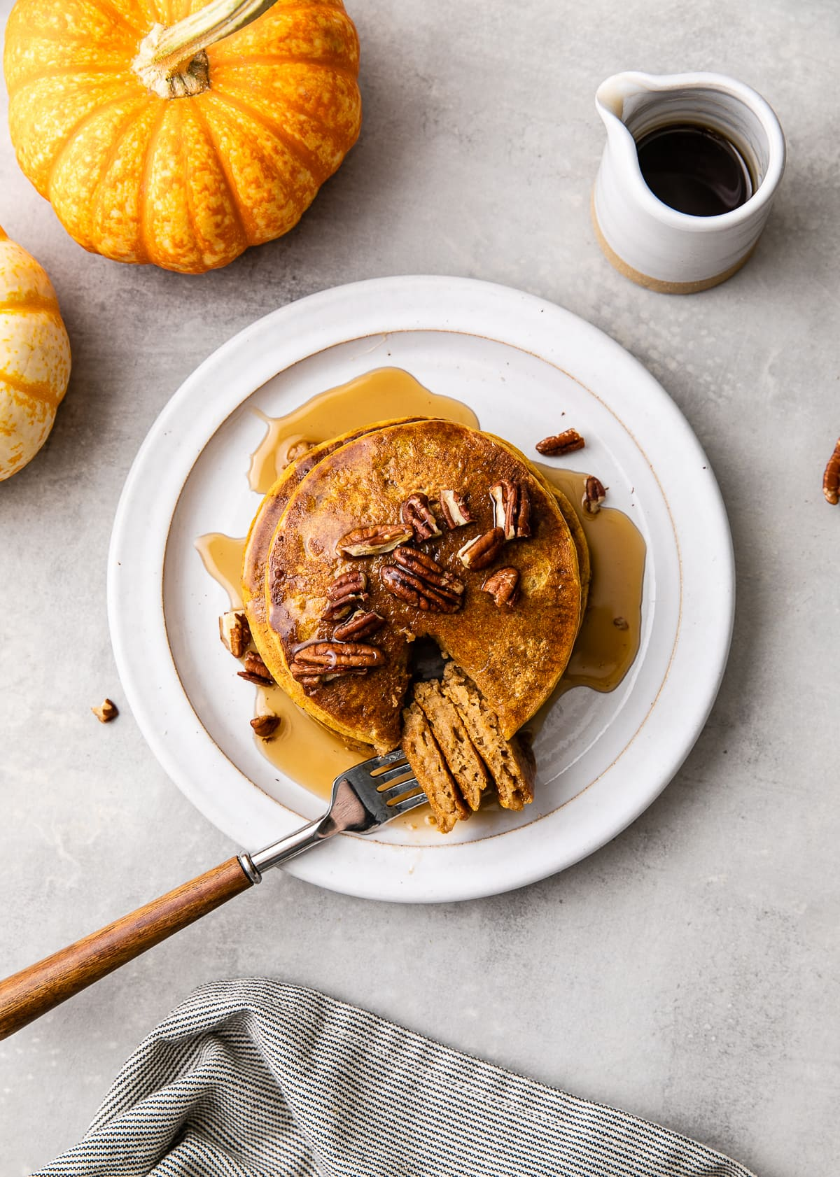 top down view of plate with pumpkin pancakes with bite on a fork and items surrounding.