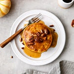 top down view of vegan pumpkin pancakes with pure maple syrup on a plate.