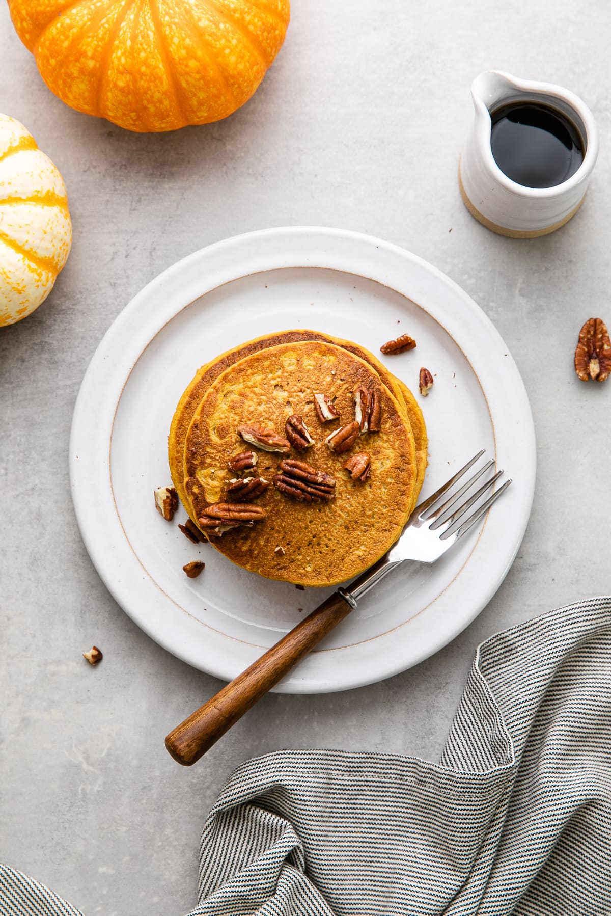 top down view of freshly made pumpkin pancakes on a plate with fork and items surrounding.