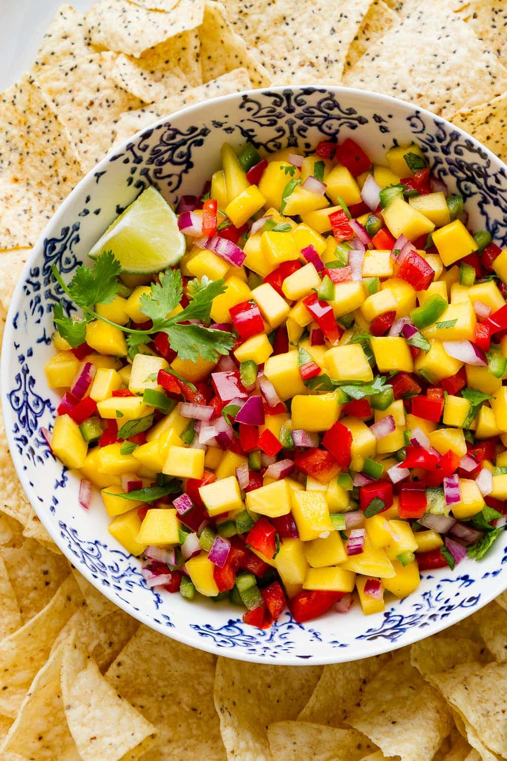 top down view of fresh mango salsa in a bowl surrounded with tortilla chips.
