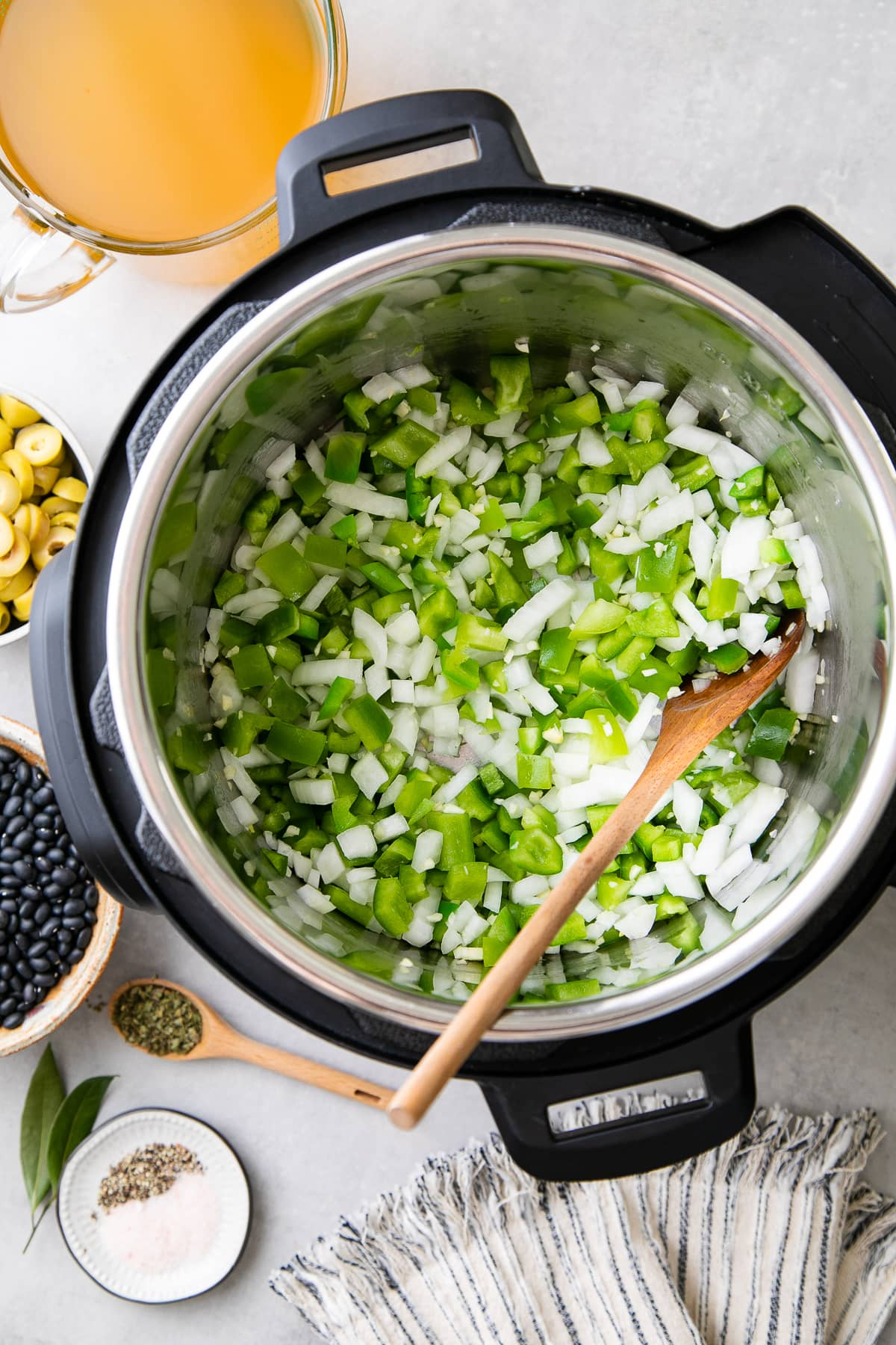 top down view of onion and bell pepper sauteed in instant pot with items surrounding.
