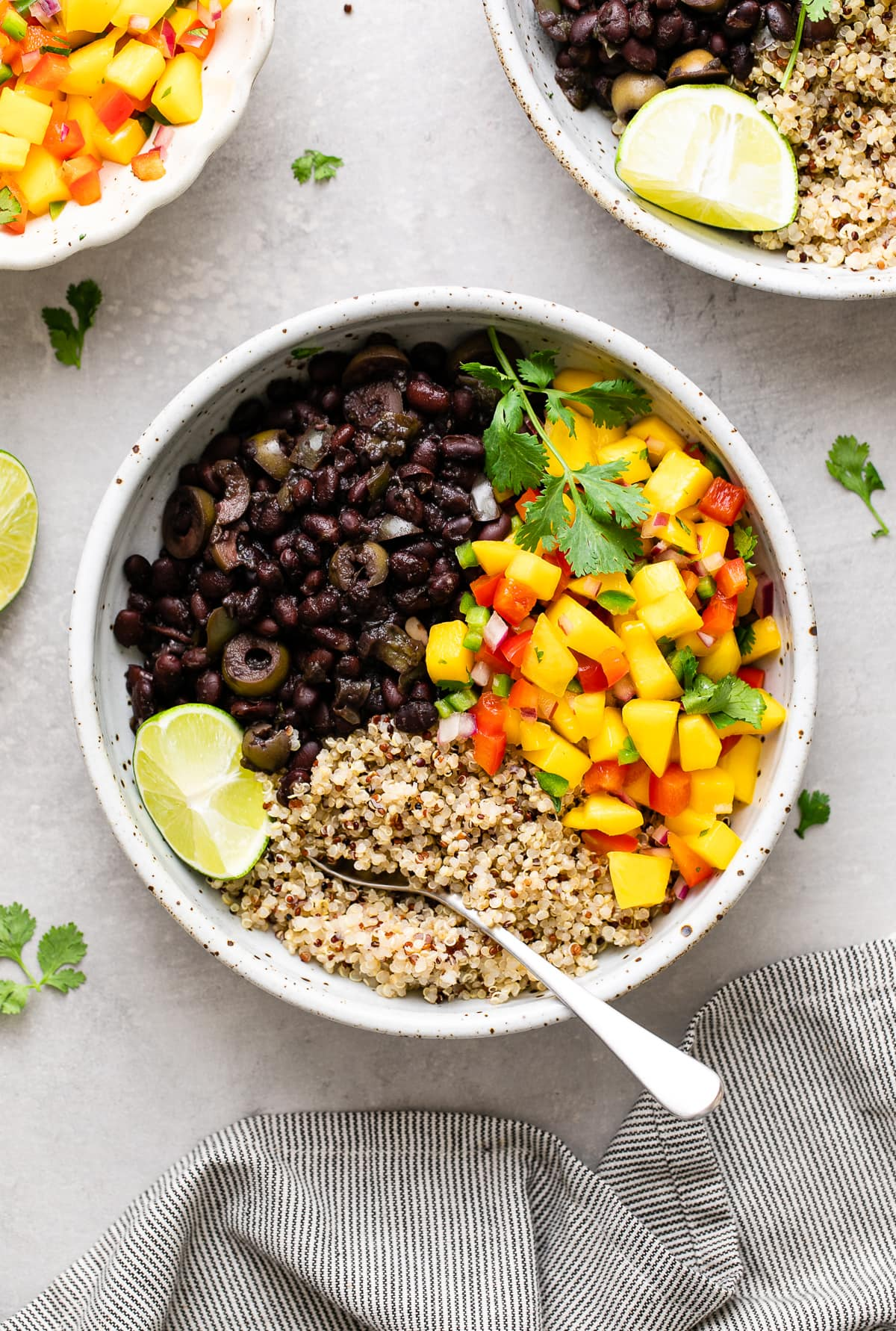 top down view of bowl with serving of cuban black bean mango bowl with quinoa with items surrounding.