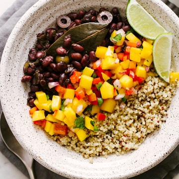 top down view of cuban black beans with mango salsa and quinoa in a bowl.