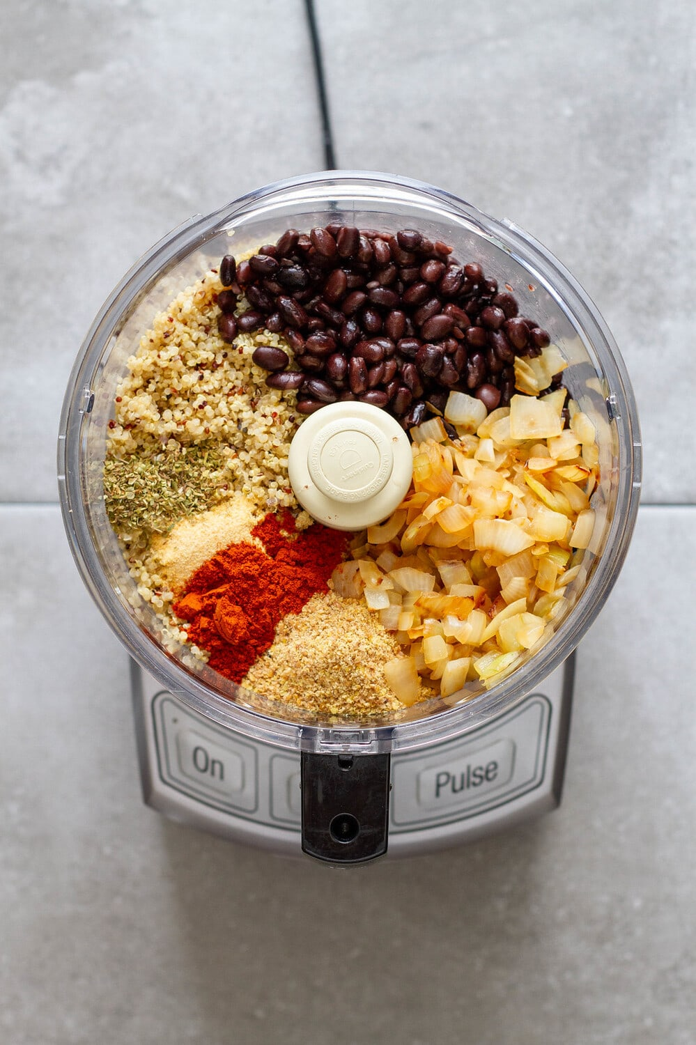 top down view of ingredients for vegan black bean burgers in a food processor.