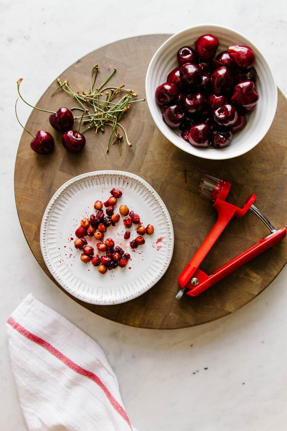 cherries being pitted on a circular wooden cutting board
