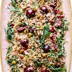 top down view of cherry mint pistachio quinoa salad on a pink platter with gold rim