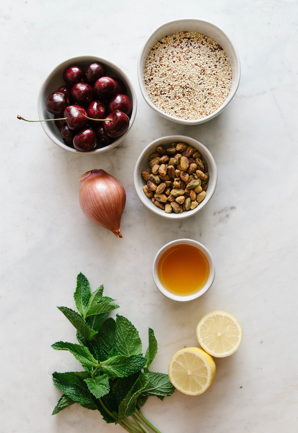 ingredients for cherry pistachio mint quinoa salad on a marble slab