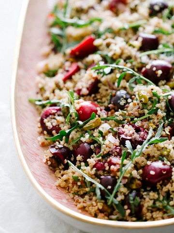 slanted shot of cherry pistachio mint and quinoa salad on a pink platter