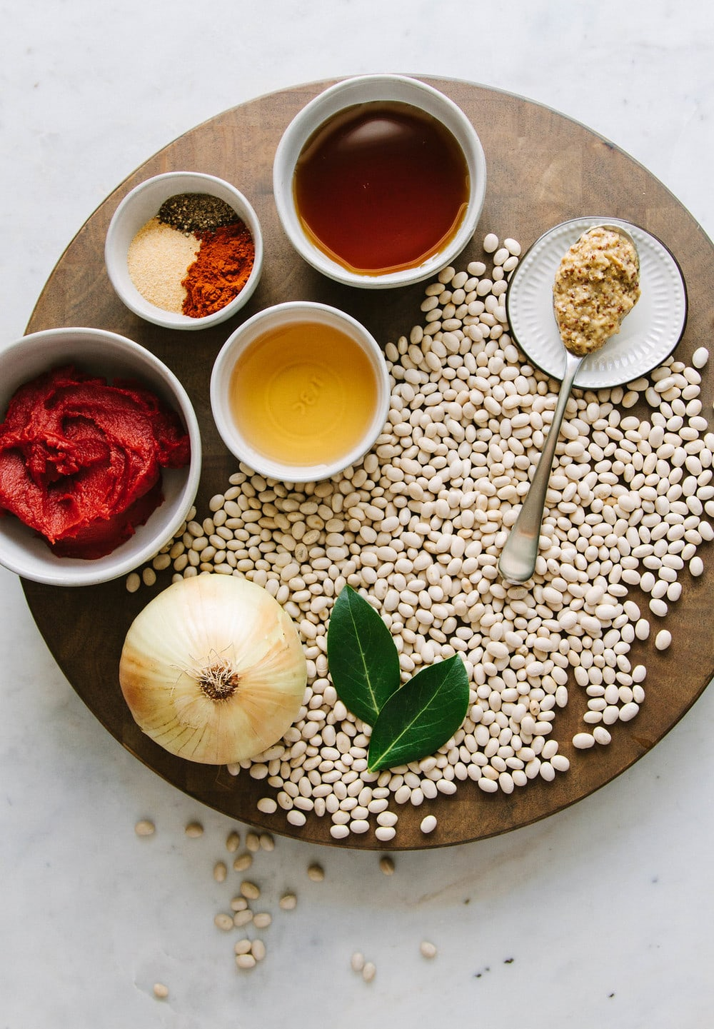 ingredients for baked beans on a circular wooden cutting board
