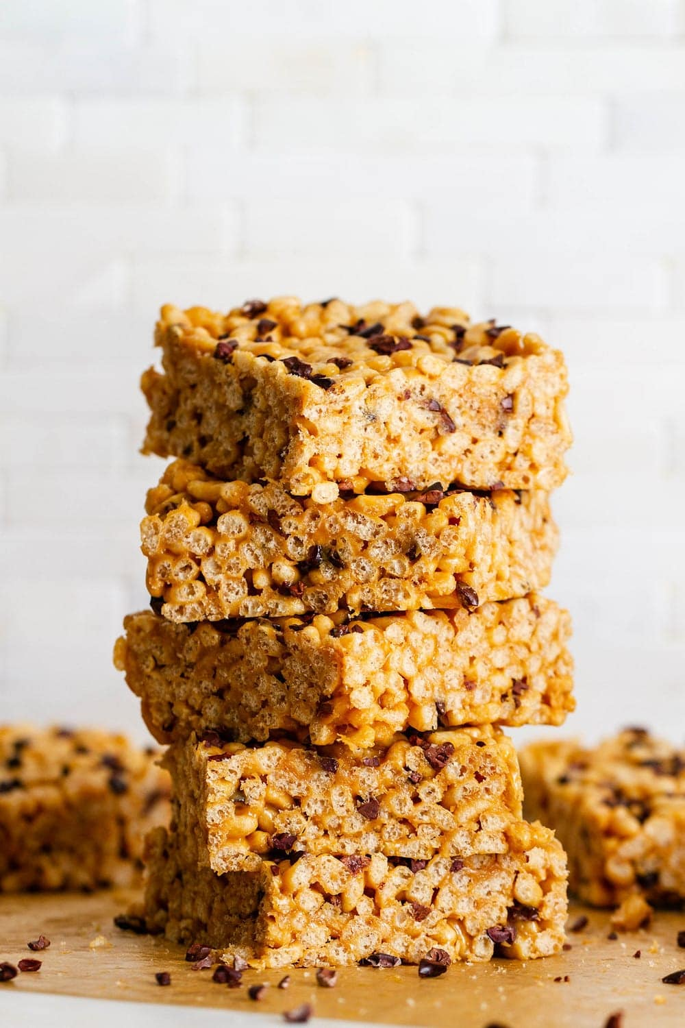 head on shot of peanut butter cacao nibs rice crispy treats cut into pieces and stacked