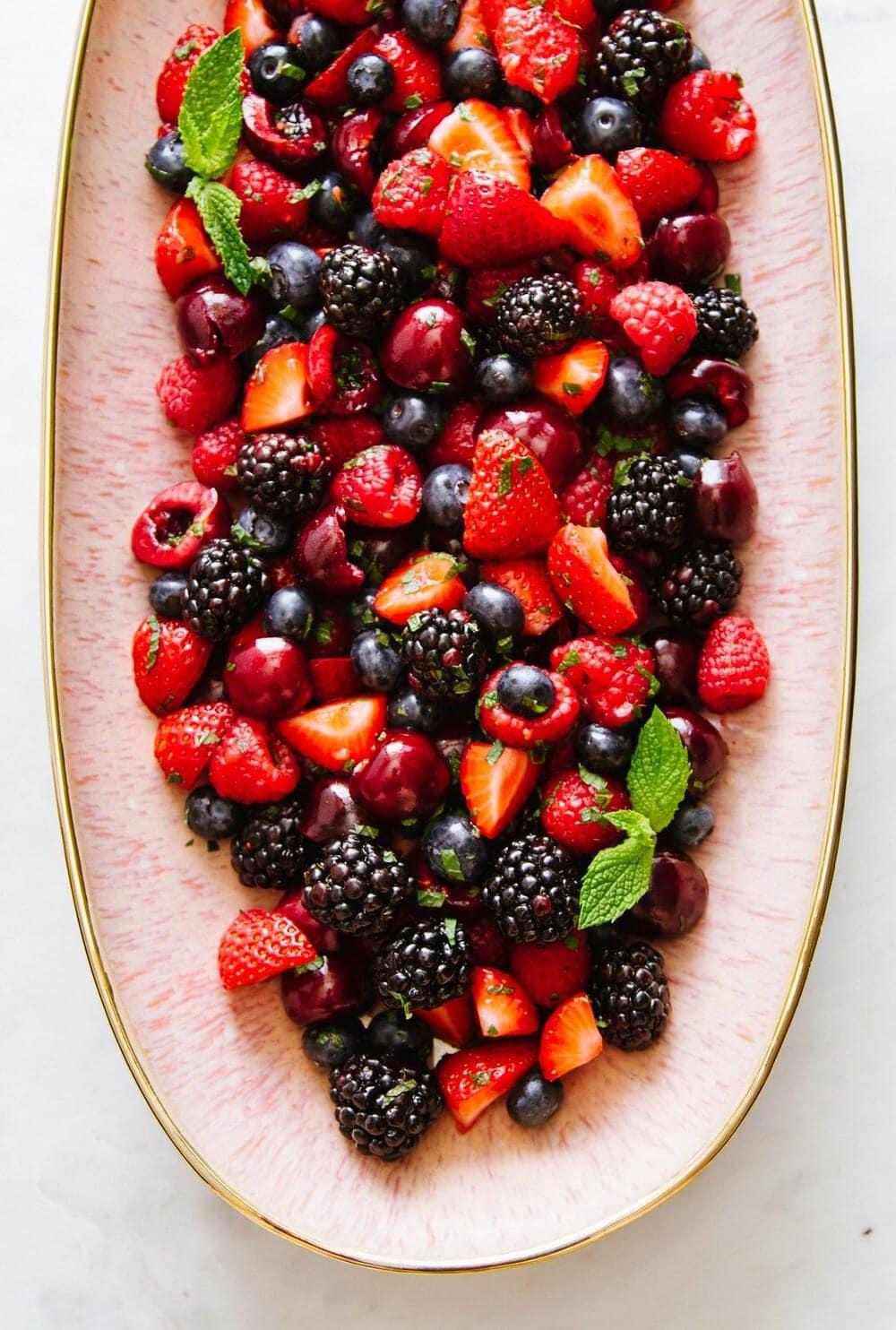 summer cherry berry fruit salad on a pink platter