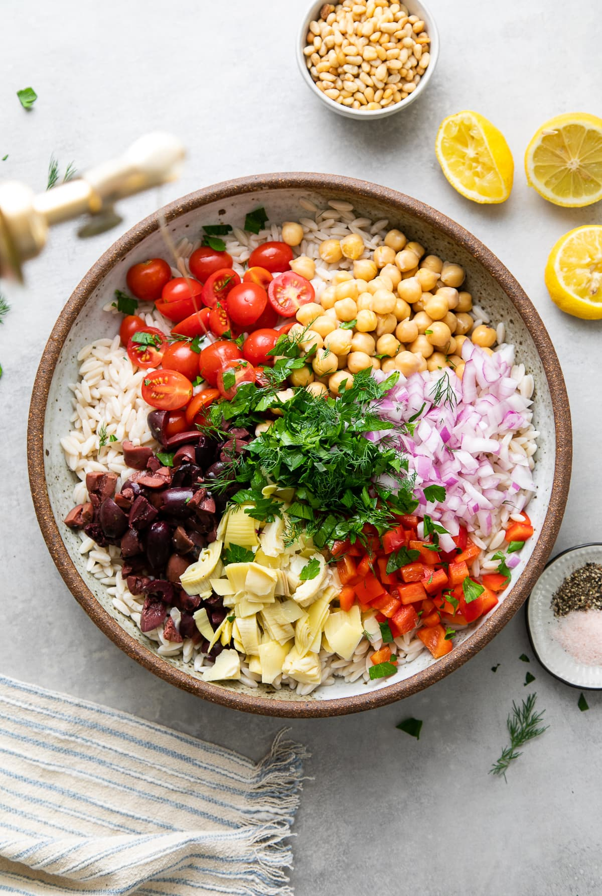 top down view showing the process of making best Mediterranean orzo salad.