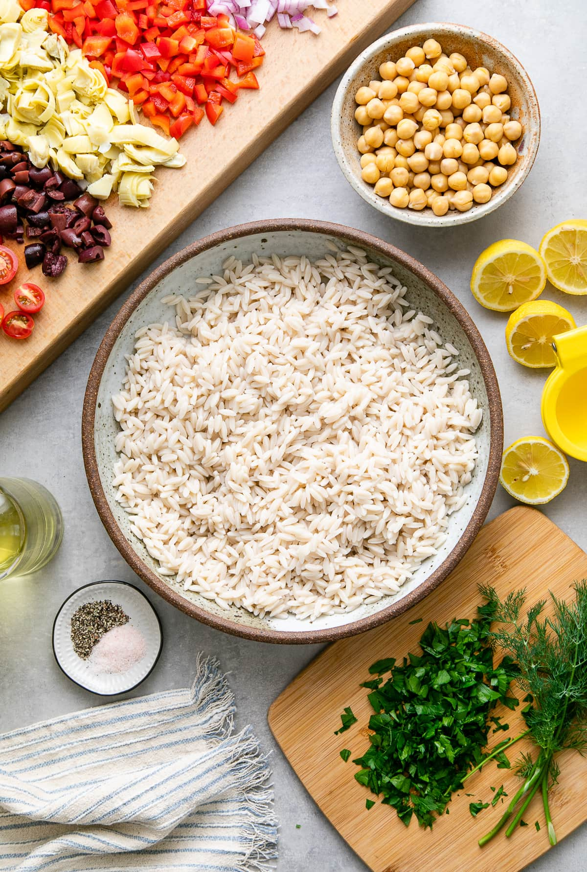 top down view of orzo cooked and ingredients prepped before mixing orzo salad together.