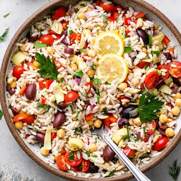 top down view of vegan Mediterranean orzo salad in a large serving bowl with spoon.