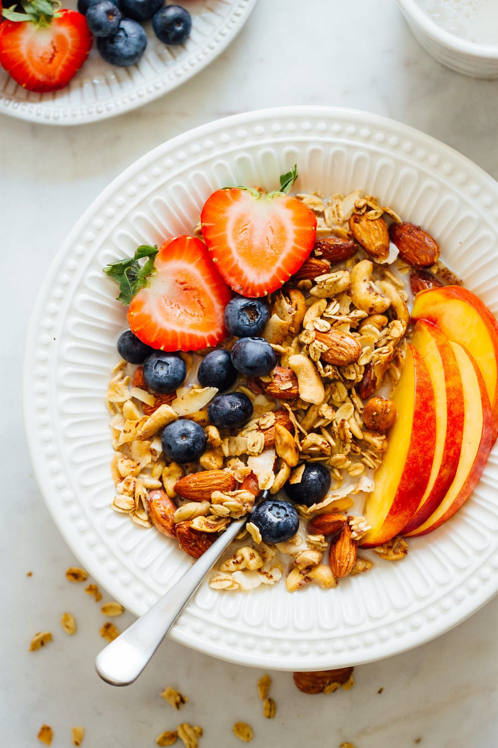 bowl of granola with fresh sliced fruit and non dairy milk