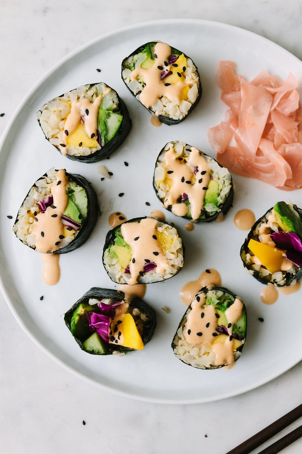 top down view mango avocado cauliflower rice sushi rolls drizzled with spicy dynamite sauce on a plate.