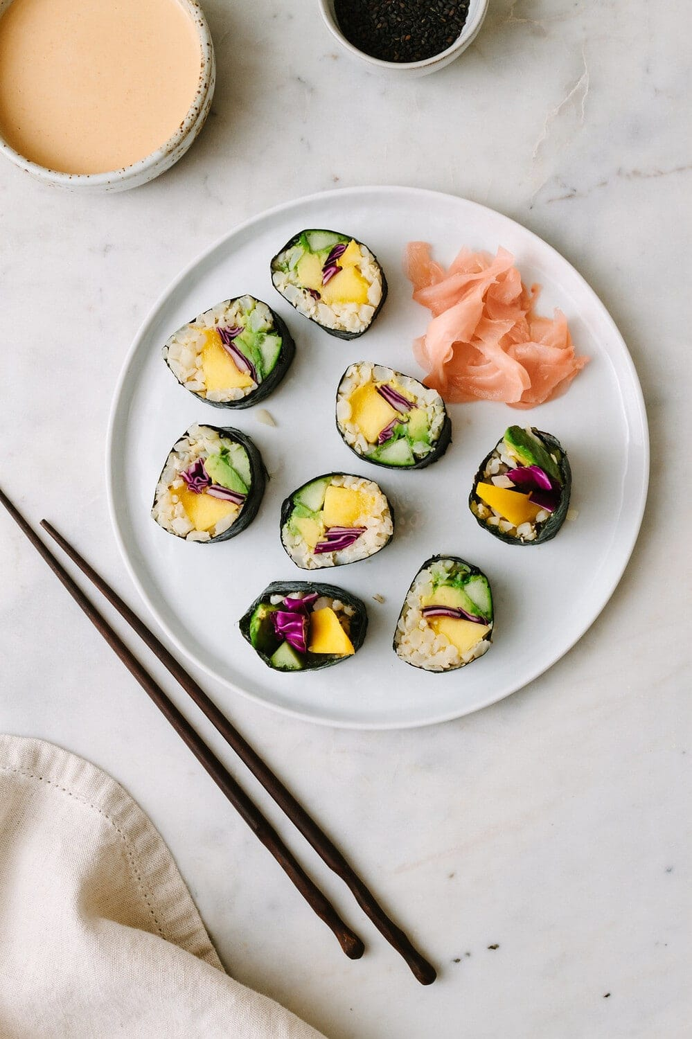 top down view of a plate full of sliced mango avocado cauliflower rice sushi rolls drizzled with spicy dynamite sauce.