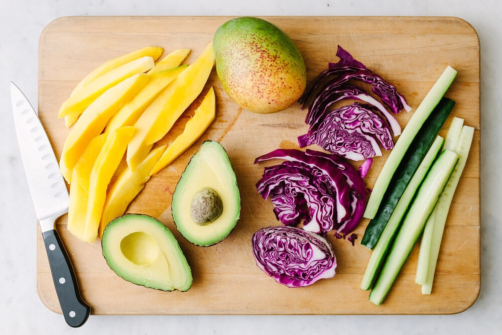 top down view of a few of the ingredients to make mango and avocado sushi rolls.