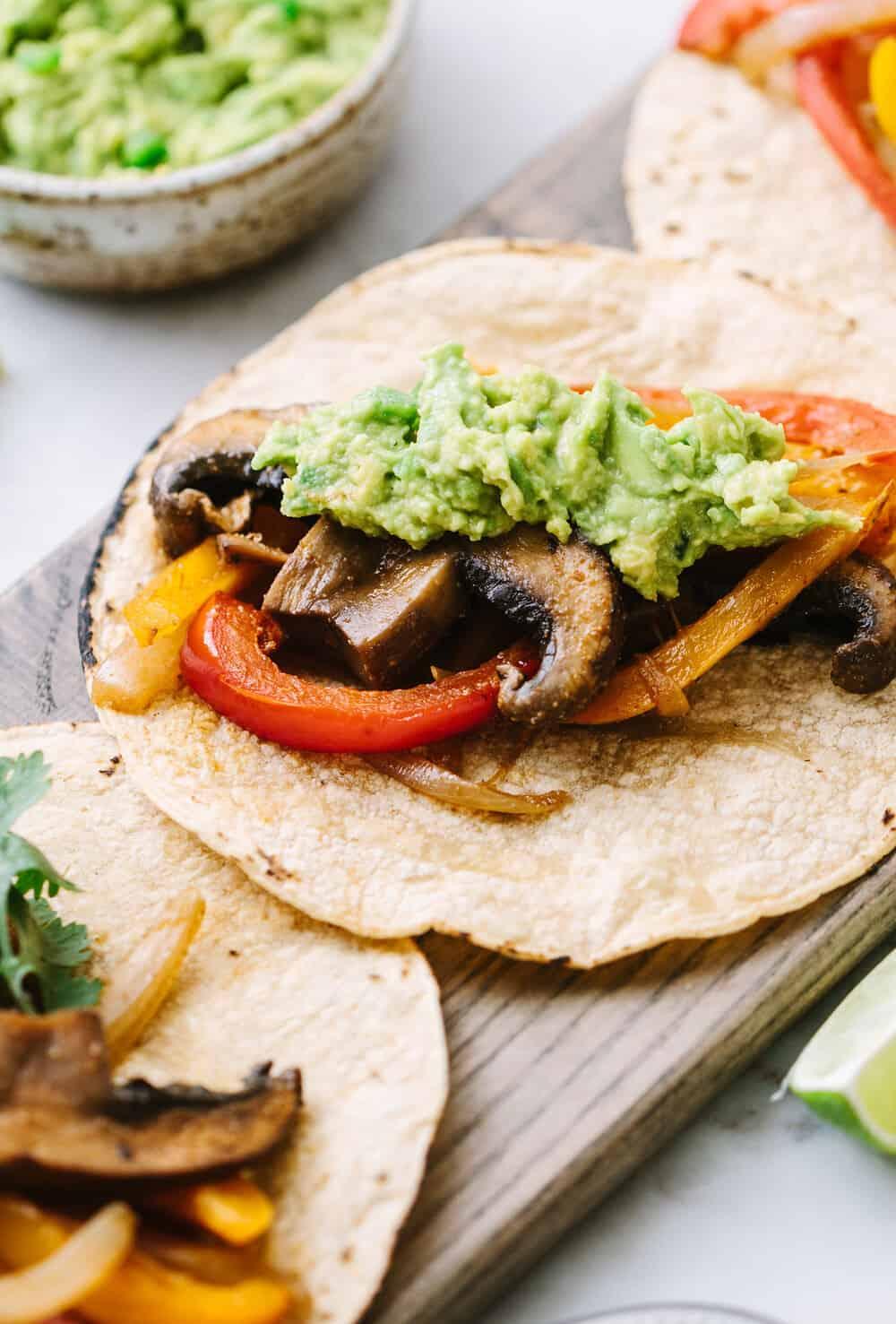 side angle view of easy portobello mushroom fajitas topped with jalapeno guacamole on corn tortillas.