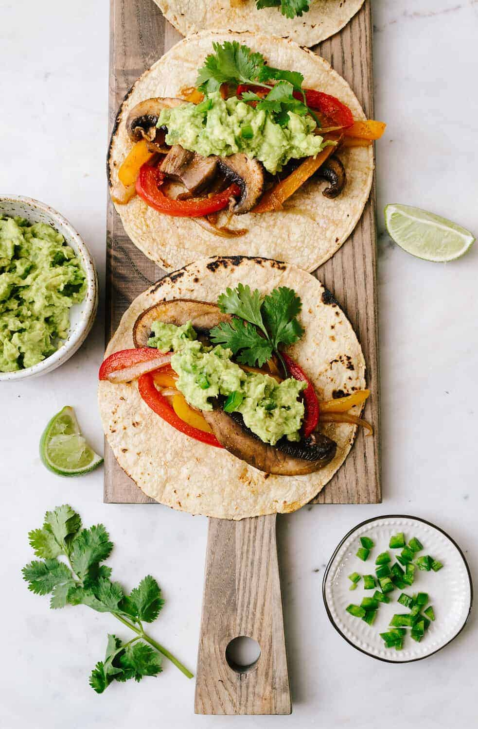 top down view of easy portobello mushroom fajitas topped with jalapeno guacamole on corn tortillas on a wooden serving board.